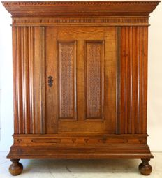Provincial single-door oak wardrobe with carved panels and hood, 18th century