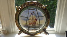 Large antique brass porthole with stained glass window.