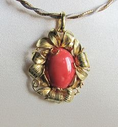 Yellow gold pendant with elliptical cabochon of Mediterranean coral.