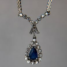 Beautiful white gold necklace with a blue drop-shaped Sapphire, surrounded by a diamonds and baguette cut diamonds of G/VVS; approx. 0,74 Ct. in total. Excellent condition.