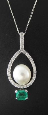 Handmade pendant set with an exclusive gold-coloured South Sea pearl and an intensely green emerald of 0.50 ct and cut diamonds, 0.50 ct in total - comes with jewellery certificate