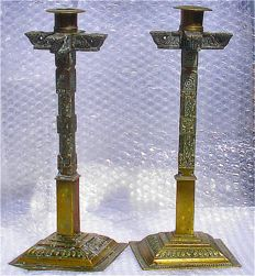 A pair of heavy cast brass candlesticks in the shape of ornate temple beams and pillars - India - 19th century