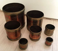 A set of antique copper and bronze measuring cups, seven pieces, made by the oriental metal pressing 'Works of Bombay', Mid 20th century