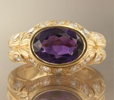 18 kt yellow gold ring set with a central, oval cut amethyst, surrounded by 14 brilliant cut diamonds, ring size 16.5 (52)