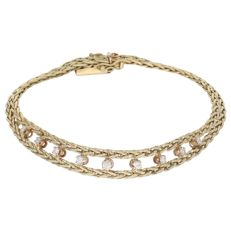 14 kt. Yellow gold decorated two-strand braided link bracelet set with nine diamonds of approx. 0.19 ct in total - Length: 19.5 cm