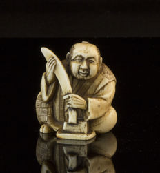 An ivory netsuke man with sword, signed - Japan - early 20th century (Meiji period)