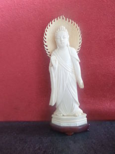 Buddha from ivory with fire wreath on wooden base – China – circa 1920