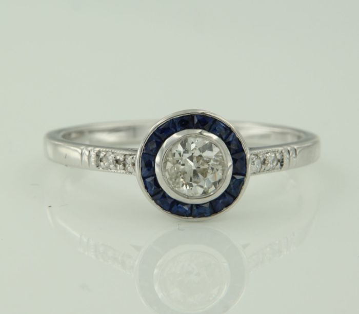 14k white gold ring set in the centre with a 0.42 ct Bolshevik cut diamond and all-around with French cut sapphires and single cut diamonds, ring size 17.25 (54).
