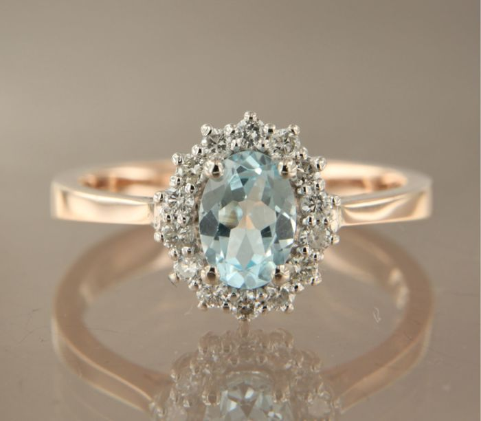 14k rose and white gold entourage ring set in the centre with an oval facet cut Topaz and 14 brilliant cut diamonds, 0.25 carat, ring size 17 (53)