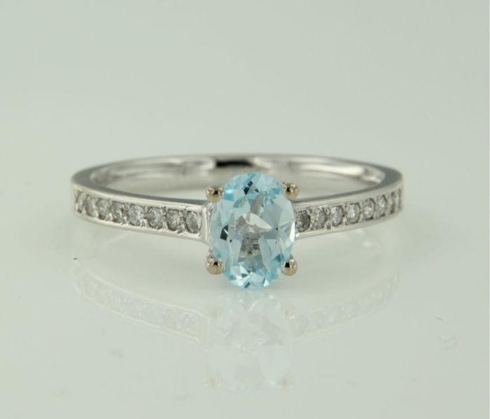 14 kt white gold ring set with a central blue topaz and 16 brilliant cut diamonds of approx. 0.18 ct in total, ring size 17.25 (54)
