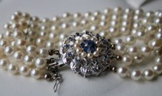 4-row Antique pearl bracelet with genuine See /Salty round ivory-white AAA+ quality pearls. Beautiful large buckle with blue Sapphires and genuine seed pearls.