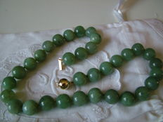 Necklace of jade spheres with gold clasp, 14 karat, 75 grams.