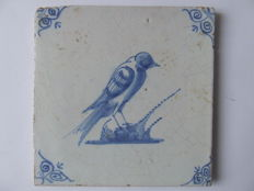 Antique tile with a depiction of a large bird and oxen head corners