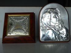 "Two items manufactured by the silversmith ""Castellani"" - a wooden frame with back support, with a plate of the Madonna and child in 925/1000 silver ""43 ""MC"" - a wooden box in walnut root with 925/1000 silver plaque with bows and flowers relief motifs."