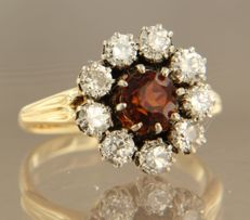 14 k bicolour entourage ring set with a central garnet and Bolshevik cut diamonds of approx. 2.30 ct in total in entourage, ring size 17.5 (55)