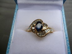 18 kt gold, 1.06 ct diamond in total, baguette cut and 0.69 ct blue oval sapphire, 19 mm.