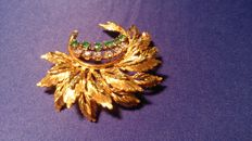 Gold brooch with brilliants and emeralds in the shape of semicircular arranged branches with a feather-like leaf pattern
