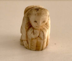 Antique ivory netsuke of a karako (Chinese child) lifting a basket – Japan – circa 1930