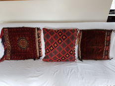 Three oriental cushions, one antique knotted, one knotted 20th century, one woven 20th century