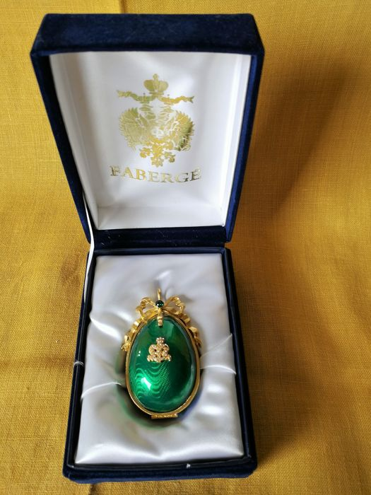 Royal green Faberge Guilloche egg with golden ring in surprise lacquer.