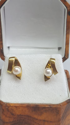 Yellow gold women's earrings set with a small salt water pearl, approx. 5 mm.
