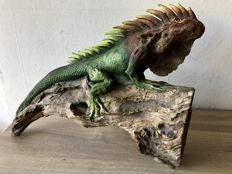 Large handmade sculpture of an iguana on a wooden tree stump