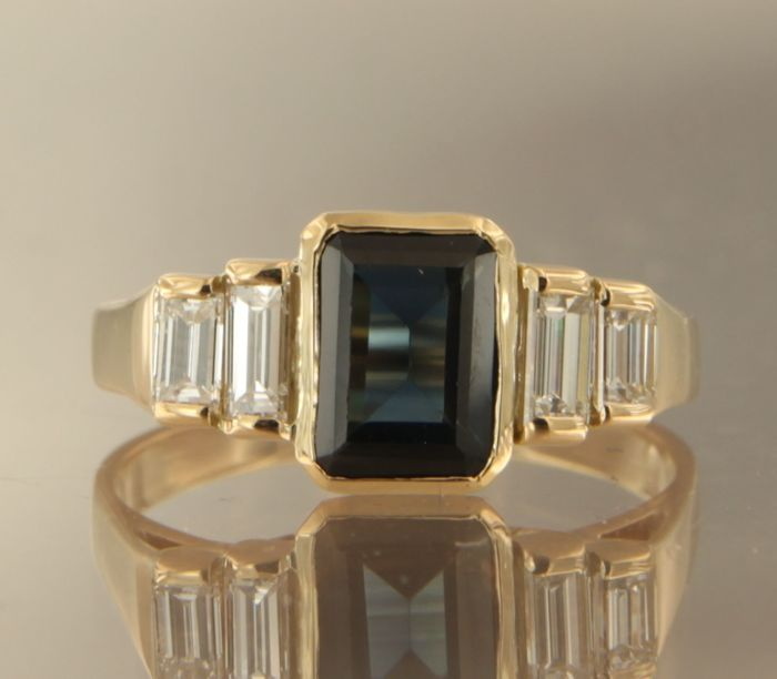 18 kt yellow gold ring set with a central emerald cut sapphire and four baguette cut diamonds, ring size 17.25 (54)