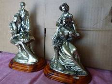 """Two pairs of youngsters, one of boyfriend and girlfriend and one of a married couple; casual the former and elegant the latter. In metal or silver coated resin, signed A Vanieli of """"Meridiana"""""""