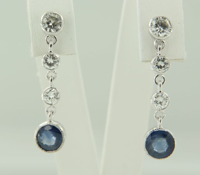 14 kt white gold dangle earrings set with sapphire and 6 brilliant cut diamonds, approx. 1.10 carat in total, size is 2.6 cm long x 6.5 mm wide.