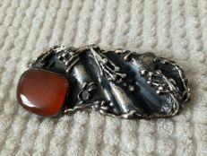 Brooch in solid silver with an amber