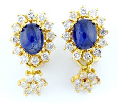 18 kt gold earrings with oval cabochon cut sapphires of 2.05 ct and 1.53 ct (VB/A) and 38 brilliant cut diamonds of 1.71 ct (I-J/P) IGE certificate.
