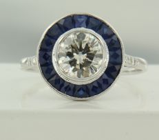 14 kt white gold ring in Art Deco style, set  in the centre with an old-Amsterdam-cut diamond of 0.92 ct with around it an entourage of sapphires and four brilliant-cut diamonds, ring size: 17.25 (54)