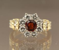 18 kt bicolour gold entourage ring centrally set with a 1.00 ct brilliant cut garnet with 14 brilliant cut diamonds around it, 1.35 ct, ring size 17 (53)