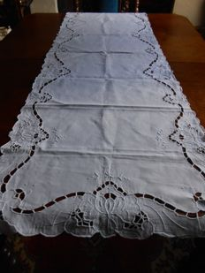 White table runner with openwork motifs.