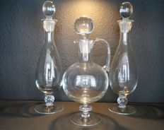 Three graceful smooth crystal carafes on foot