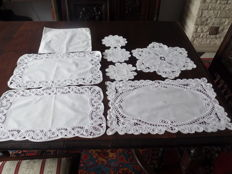 Lot of eight embroidered doilies with ribbons on the side.