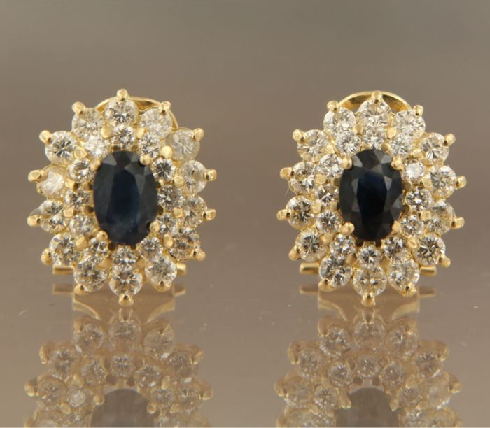 18 kt gold clip-on earrings with a central sapphire and a double entourage of brilliant cut diamonds, size 1.4 x 1.2 cm.