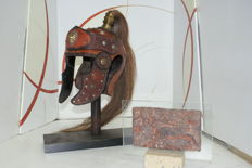 Roman helmet in hand-worked leather and original tail of horsehair with wood base; in addition the Roman coach carved on stone.