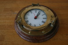 Clock in a bronze porthole with a walnut base