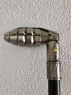 Walking stick with heavy metal handle in the shape of a hand grenade.