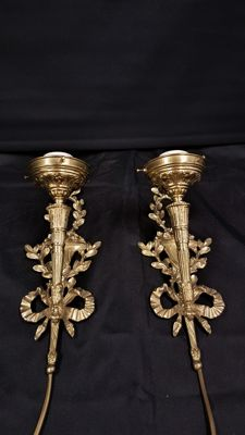 Two brass wall lights torches with a bow