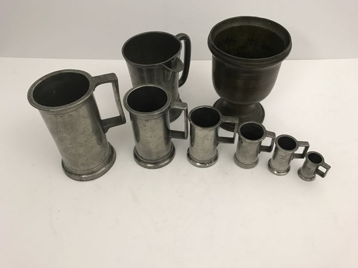 Heavy bronze mortar, six pewter measuring cups and a pewter jug