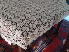 Crochet oval tablecloth in a light beige colour.