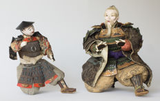 Remarkable set of 2 antique musha ningyô puppets. Minister Takenouchi-No-Sukune and a standard-bearer. With wooden swords and the accompanying storage case – Japan – early 19th century (Edo period)
