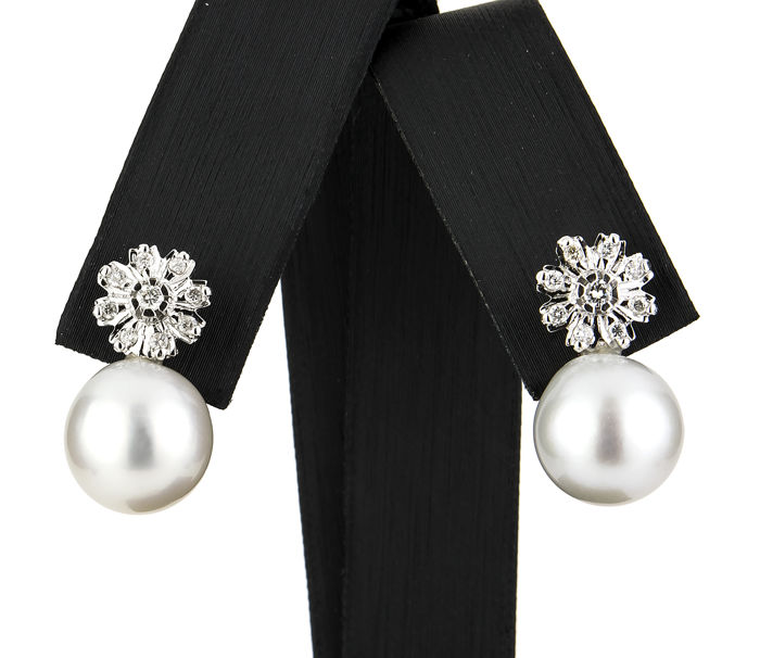 White gold earrings set with brilliant cut diamonds in a flower-shaped setting and Australian South Sea pearls
