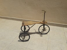 Old tricycle made of wood and iron, toy for children.