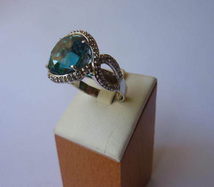 18 kt white gold ring with oval blue gemstone and diamonds. Inner shank measurement: 18 mm.