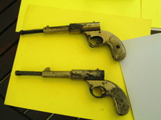 A pair of late 19th century 177 pop out dollar pistols