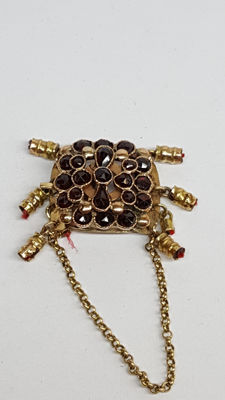 14 kt yellow gold antique clasp set with garnet and safety clasp.