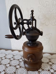 Old coffee grinder with a big wheel, made of cast iron and wood, France, 1960/70.
